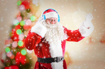 Santa Claus with headphones listening to Christmas music and snow effect on blurred background
