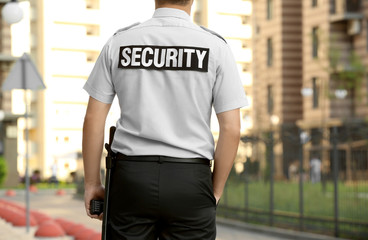 Male security guard standing outdoors