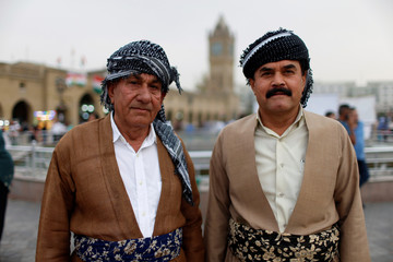 Two Kurdish men pose for the camera in a square in the old city of Erbil