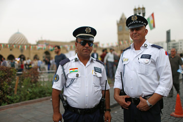 Two Kurdish traffic police officers pose for the camera in a square in the old city of Erbil
