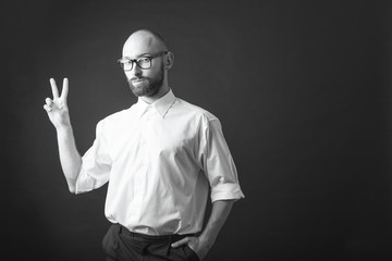young white beard wearing glasses man white shirt black pants studio monochrome background