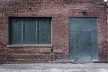 Green window and door on a red brick wall