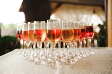 A lot of wine glasses with a cool delicious champagne or white wine at the bar. Alcohol background.