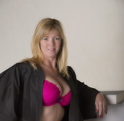 Portrait of a female mature student wearing a black gown and a revealing cleavage