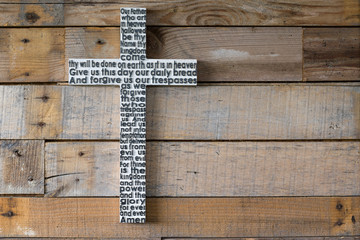 White wooden cross with the Lord's prayer on the shabby  natural wooden  plank.