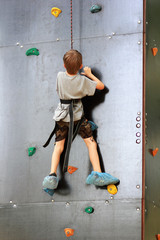 Five year old boy learning to climb the rock mountain wall in the summer park outside. Bouldering.