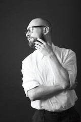 young white beard wearing glasses man white shirt black pants studio monochrome background
