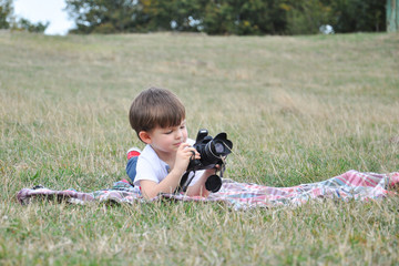 Four years old boy taking photos with camera. Little photographer with professional dslr camera