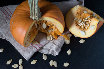 sliced fall pumpkin with seeds on dark background closup