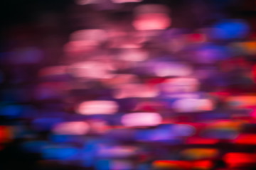 Abstract background of colorful blurs in motion on black. Bokeh of defocused streaks, blurred neon blue, orange and red leds, glowing city lights, wallpapers and banners