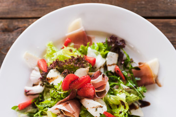 Fresh green salad with parma ham, blue cheese and strawberry serving in restaurant on wooden table. Gourmet cuisine close up top view picture