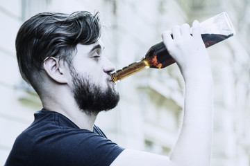Young male with alcoholic drink. Drunk young people (alcoholism, pain, pity, hopelessness, social problem of dependence concept)