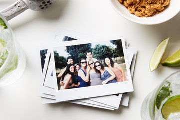 Pile of printed photos with friends in garden posing at camera