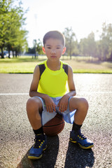 Asian kid sitting on a basketball in an outdoor basketball court