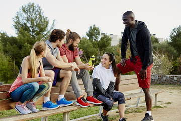 Group Of Athletes Relaxing After Workout In Park