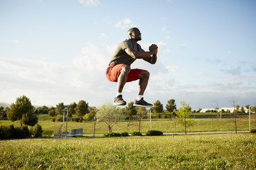 Determined Male Athlete Jumping In Park