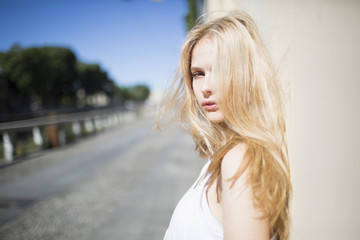Candid blonde girl leaning against the wall