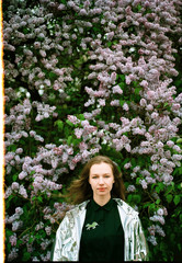 Portrait of young woman among lilac in blossom