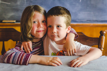 Siblings hugging at the kitchen table
