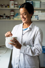 Woman pharmacist making some drugs in a drugstore background