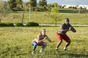 Determined Athletes Doing Squats On Grass In Park