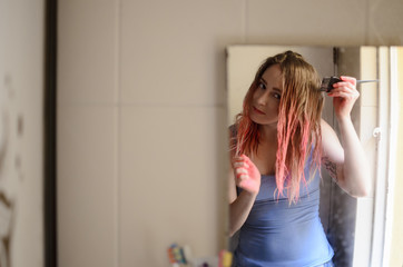 Reflection of a blond young female dying her hair pink in the bathroom