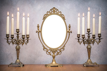 Retro old makeup mirror frame and burning candles in candlesticks on wooden table. Vintage style filtered photo