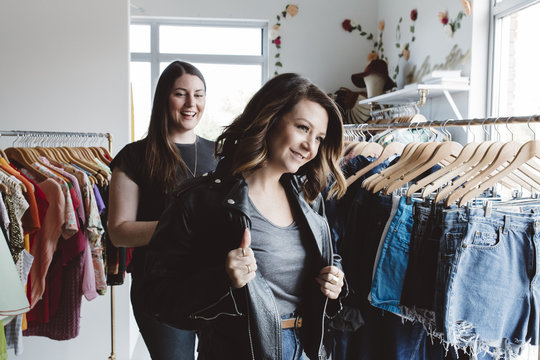 Woman trying on leather jacket in cute boutique