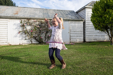 Cute little girl with specs playing with hula hoop