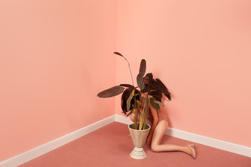 woman in a pink room hiding behind a plant