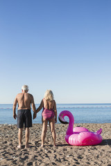 Senior couple with flamingo float on the beach