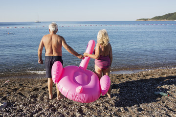Elderly couple and a flamingo float on the beach