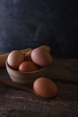 Fresh hens eggs in a bowl on a wooden table.