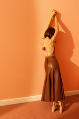 woman with long leather skirt leaning against a wall