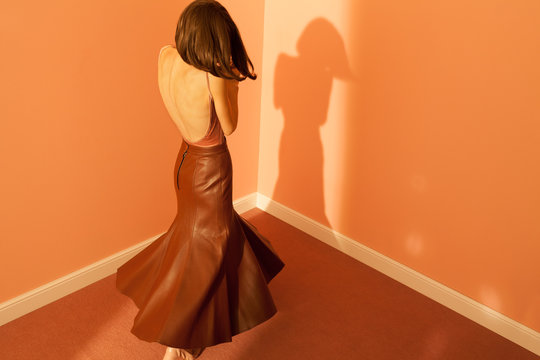 Woman in long leather skirt dancing in room