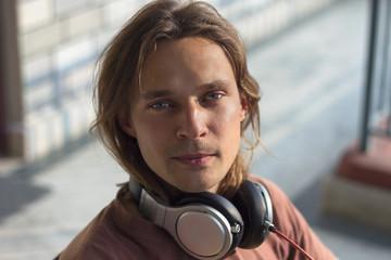 Portrait of handsome guy with headphones around his neck