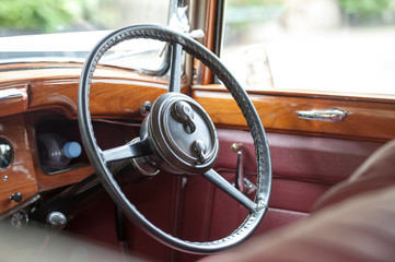 steering wheel and wood and leather interior of a vintage car