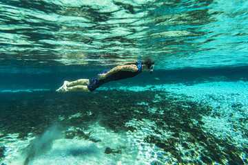 A teenager snorkeling in a fresh water spring in Florida
