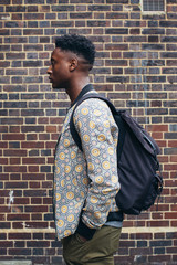 Profile of Young Fashionable Black Man Standing in Front of Exposed Brick Wall
