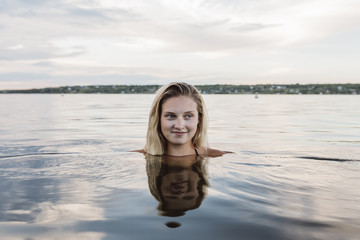 Pretty young woman in calm lake