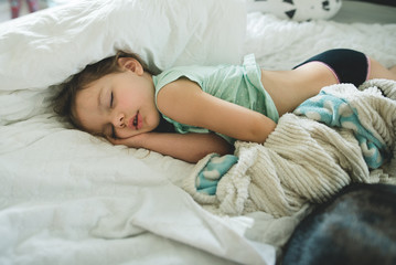 Toddler girl passed out in bed