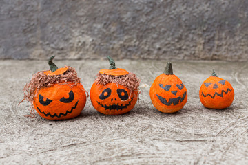 Artificial orange pumpkins on a gray background. Evil pumpkins. Background for Halloween.