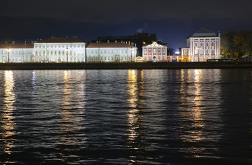 Night view of the University embankment of St. Petersburg through the Neva River