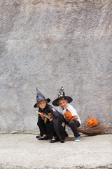 Girl and boy in Halloween costumes having fun. Brother and sister a witch costumes are playing with a pumpkin outdoor. Children playing with a broom