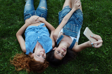 Two best friends laying in the grass taking pictures with their phone