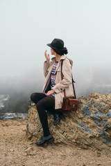 Wind-haired brunette in hat sitting on rock on top of San Francisco Twin Peak viewpoint
