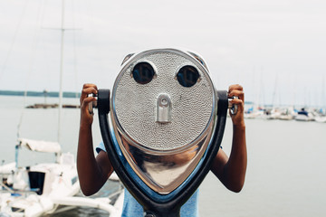 Black girl looking through binoculars by a bay