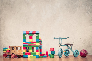 Retro old toys: wooden house made of construction blocks, truck, trike bicycle and leather ball front concrete textured wall background. Vintage instagram style filtered photo