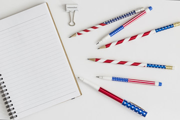 "Blank notebook, stars and stripes pens and pencils and paper clip saying ""remember"""