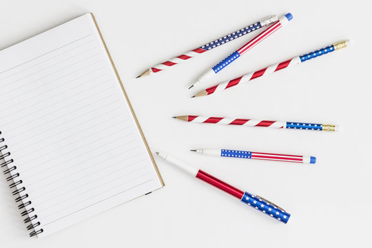 Open notebook and stars and stripes pens and pencils